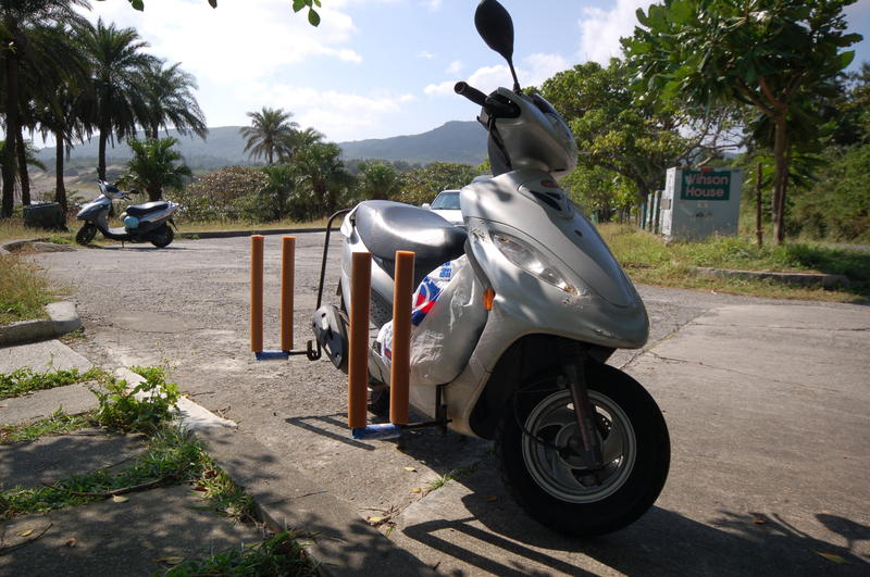 Surfboard holding motorcycle.