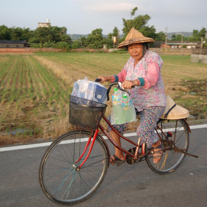 Farmer lady riding bike.
